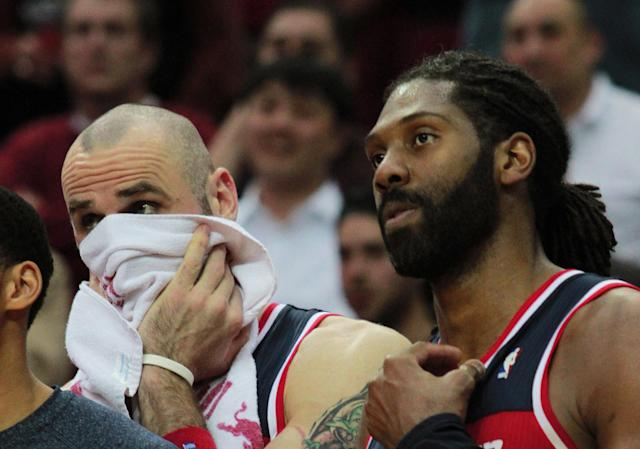 Washington Wizards Martin Gortat, left, and forward Nene, right, watch from the bench as their team loses to the Houston Rockets 113-112 in the final seconds of an NBA basketball game in Houston, Wednesday, Feb. 12, 2014. (AP Photo/Richard Carson)