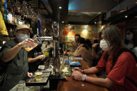 """In this Oct. 9, 2020 photo, former lawmaker and pro-democracy activist Leung Kwok-hung, known as """"Long Hair,"""" right, waits for his drink at Club 71 in Hong Kong. The bar known as a gathering place for pro-democracy activists and intellectuals is closing. For years, the storied bar has served as a watering hole for the city's pro-democracy activists and intellectuals, who could freely engage in discussions over a round of beer or two. (AP Photo/Kin Cheung)"""