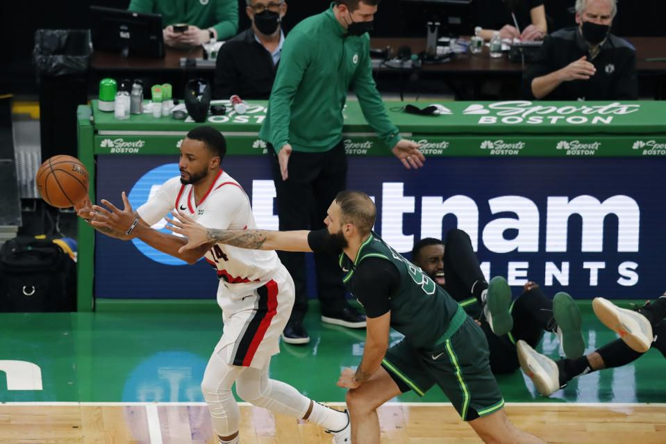 Boston Celtics' Evan Fournier (94) defends against Portland Trail Blazers' Norman Powell (24) as Boston Celtics' Jaylen Brown, behind right, collides with Jayson Tatum, far right, as head coach Brad Stevens reacts during the second half of an NBA basketball game, Sunday, May 2, 2021, in Boston. (AP Photo/Michael Dwyer)