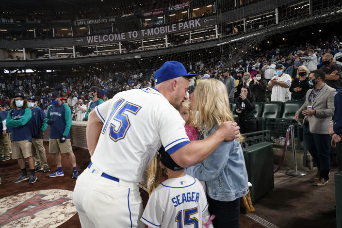 Seattle Mariners third baseman Kyle Seager (15) kisses his wife Julie Seager after a baseball game against the Los Angeles Angels Sunday, Oct. 3, 2021, in Seattle. The Angels won 7-3. The game was potentially Seager's final game. (AP Photo/Elaine Thompson)
