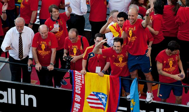 MADRID, SPAIN - JULY 02: Coach Vicente del Bosque (L) and players Juanfran (4th R), Raul Albiol (3rd R), Pepe Reina (2nd R) and Cesc Fabregas (R) of Spain celebrate with the UEFA EURO 2012 trophy on a double-decker bus during the Spanish team's victory parade on July 2, 2012 in Madrid, Spain. Spain beat Italy 4-0 in the UEFA EURO 2012 final match in Kiev, Ukraine, on July 1, 2012. (Photo by Pablo Blazquez Dominguez/Getty Images)