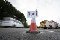 Vehicles arrive at a petrol station, in Manchester, England, Tuesday, Sept. 28, 2021. Thousands of British gas stations have run dry, as motorists scrambled to fill up amid a supply disruption due to a shortage of truck drivers. Long lines of vehicles formed at many gas stations over the weekend, and tempers frayed as some drivers waited for hours. (AP Photo/Jon Super)