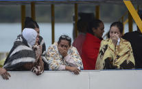 <p>People who survived a sunken ferry, cry as they wait for more information about their missing friends and relatives, at a reservoir in Guatape, Colombia, Sunday, June 25, 2017. (Luis Benavides/AP) </p>