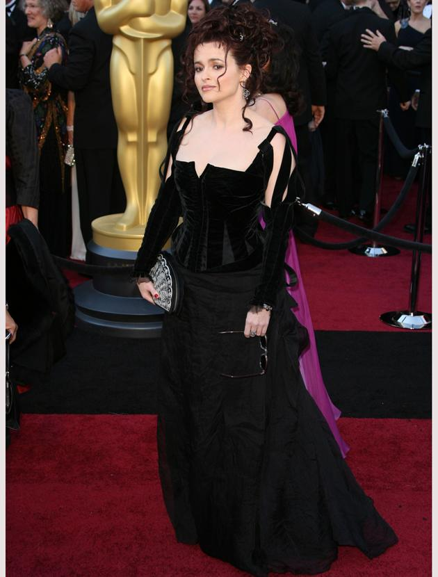 Oscars 2011 photos: Quirky dresser Helena Bonham Carter dressed relatively demurely in a Colleen Atwood black dress and a fan clutch.