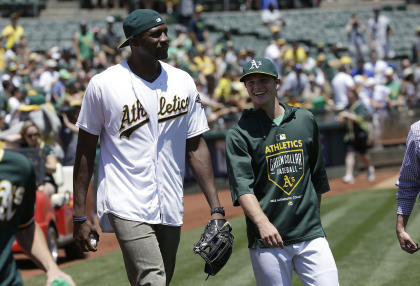 Festus Ezeli, left, prepares to throw out the first pitch before an Oakland A's game on July 5. (AP)