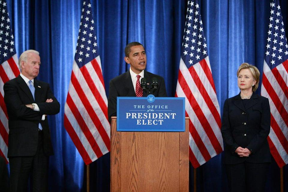 Vice-President-elect Joe Biden (L) listens as President-elect Barack Obama introduces members of his National Security Team including Senator Hillary Clinton (R) (D-NY) as his choice for secretary of state during a press conference at the Hilton Hotel December 1, 2008 in Chicago, Illinois. (Photo by Scott Olson/Getty Images)