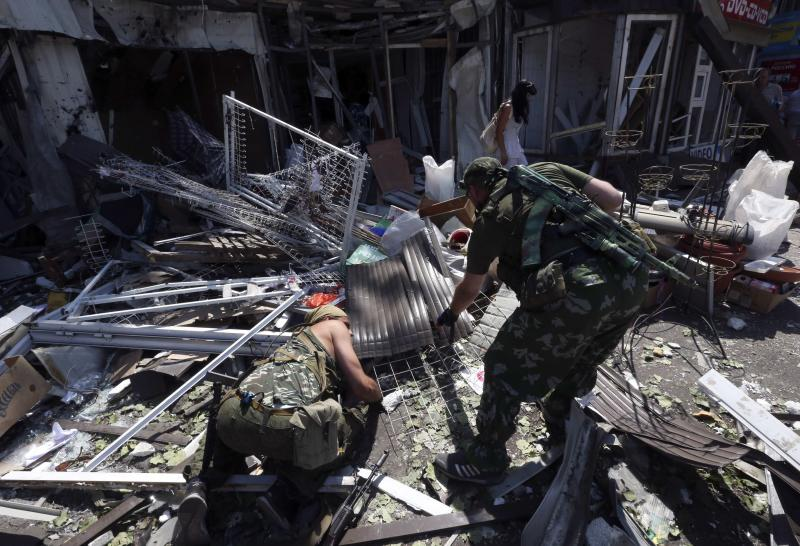 Armed pro-Russian separatists inspect wreckage near a damaged building following what locals say was a recent airstrike by Ukrainian forces in Donetsk