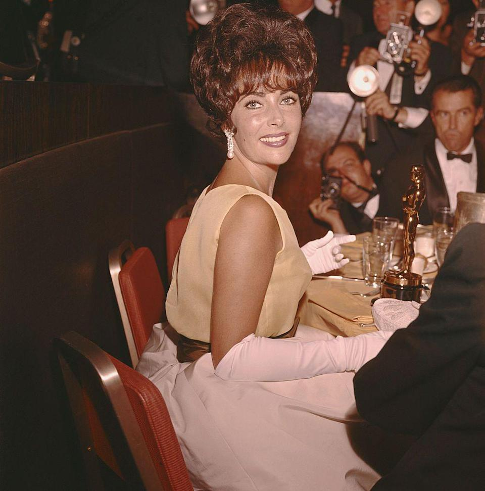 <p>Elizabeth smiles while her Academy Award for Best Actress in <em>Butterfield 8</em> rests on the table. </p>