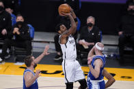 Brooklyn Nets guard Kyrie Irving, center, shoots from between Los Angeles Lakers guard Alex Caruso, right, and center Marc Gasol during the first half of an NBA basketball game Thursday, Feb. 18, 2021, in Los Angeles. (AP Photo/Marcio Jose Sanchez)