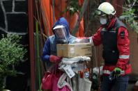 A member of Civil Protection accompanies a resident after recovering his belongings from an apartment building damaged by an earthquake that struck southern Mexico on Tuesday, in Mexico City