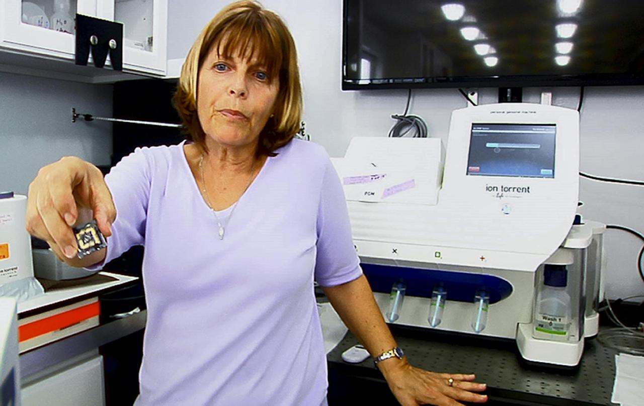 This image from video, taken March 29, 2014, shows University of Florida molecular biologist Andrea Kohn in front of a genomic sequencing machine attached to a special tilting tabletop that bobs with rough waves in this shipboard laboratory during a sail in the Gulf Stream off the coast of Florida. The lab is part of a research project to decode the genomic blueprints of fragile marine life in real time _ on board the ship where they were caught. (AP Photo/Suzette Laboy)