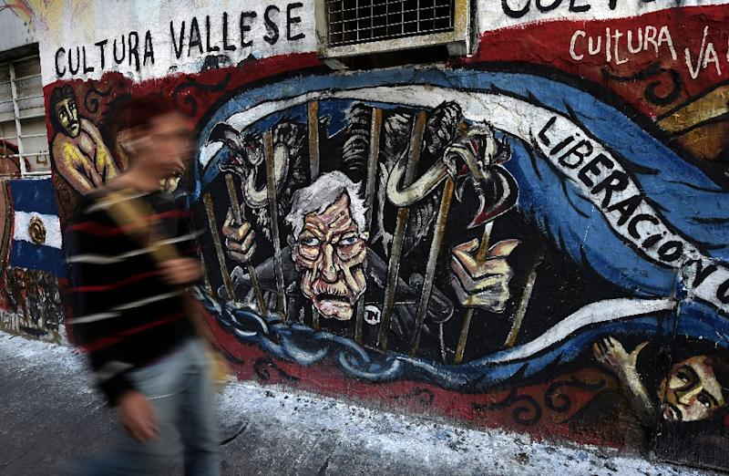 A man walks next to a grafitti depicting US Judge Thomas Griesa and vultures behind bars, outside the National Congress in Buenos Aires on September 10, 2014 (AFP Photo/Juan Mabromata)