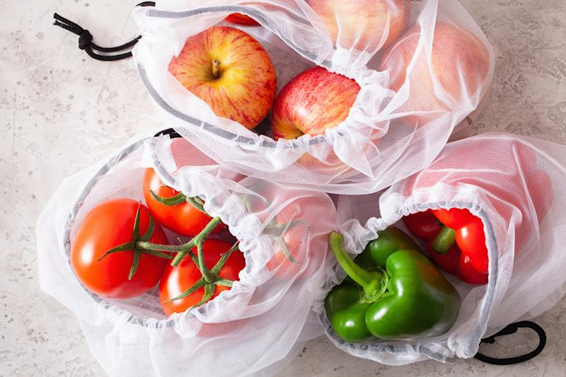 apples tomatoes bell peppers vegetables in reusable mesh nylon bag, plastic free zero waste concept