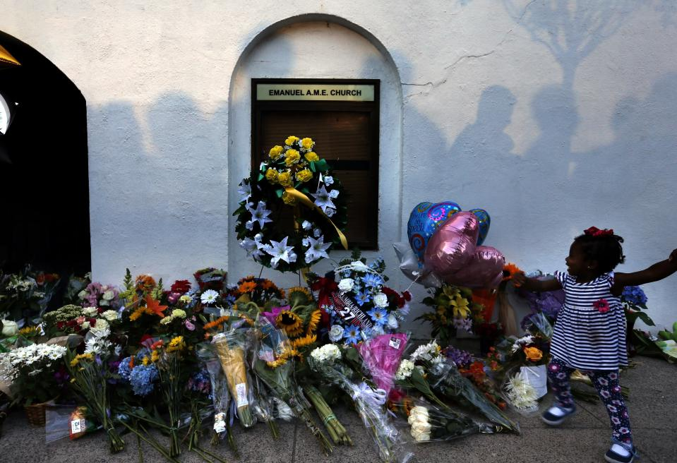 FILE - In this Thursday, June 18, 2015, file photo, mourners pass by a makeshift memorial on the sidewalk in front of the Emanuel AME Church following a shooting by Dylann Roof in Charleston, S.C. South Carolina is one step closer to becoming the 48th state in the nation to pass a hate crime law. House representatives gave key approval by a 79-29 vote Wednesday, April 7, 2021, on the proposal to allow harsher penalties for certain crimes motivated by hatred. (AP Photo/Stephen B. Morton, File)