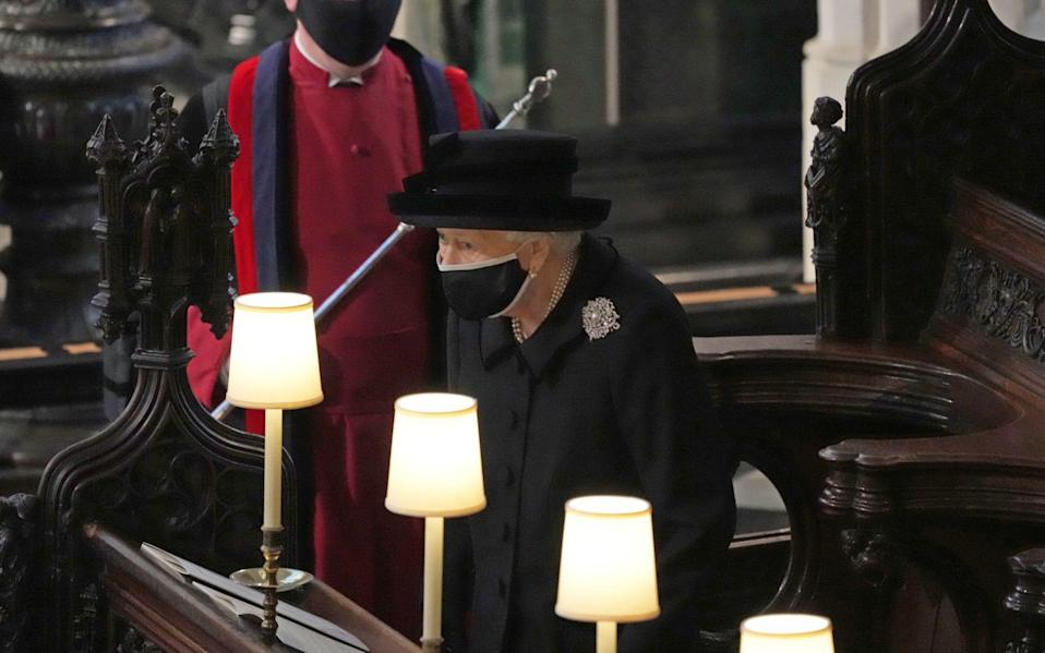 Queen Elizabeth II takes her seat in St George's Chapel away from other family members