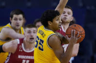 Michigan guard Eli Brooks (55) looks to pass the ball as Wisconsin guard Brad Davison, right, and forward Micah Potter (11) defend during the first half of an NCAA college basketball game Tuesday, Jan. 12, 2021, in Ann Arbor, Mich. (AP Photo/Carlos Osorio)