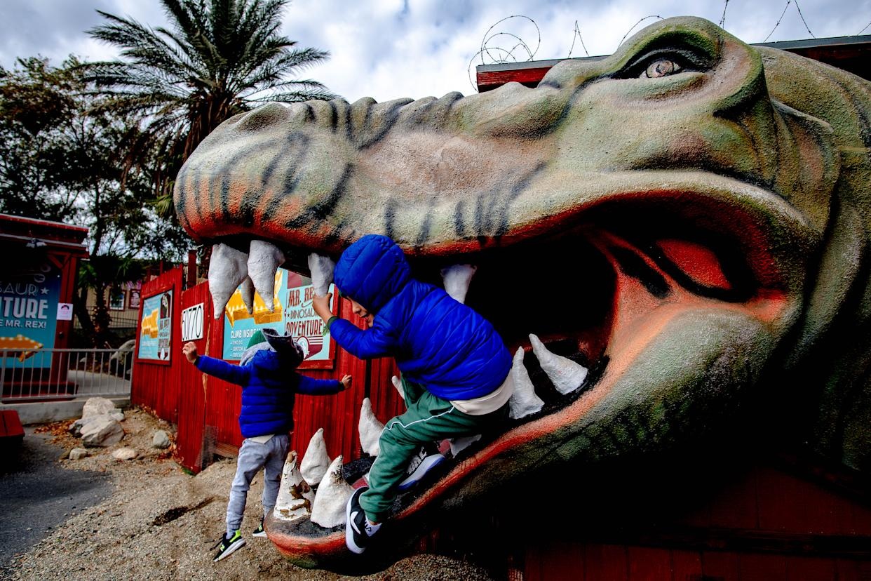 CABAZON, CA - JANUARY 27: Omar Abouzahr, 5, front, and brother Fahed, 7, of Corna play in the mouth of a concrete dinosaur at the Cabazon Dinosaurs attraction in Cabazon on Wednesday, Jan. 27, 2021. (Photo by Watchara Phomicinda/MediaNews Group/The Press-Enterprise via Getty Images)