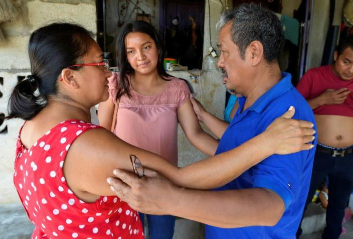 Friends embrace Gerardo Zacarias, who fears his daughter Paola Damaris is among the 19 bodies found shot and burnt in a remote part of northern Mexico, in Catarina