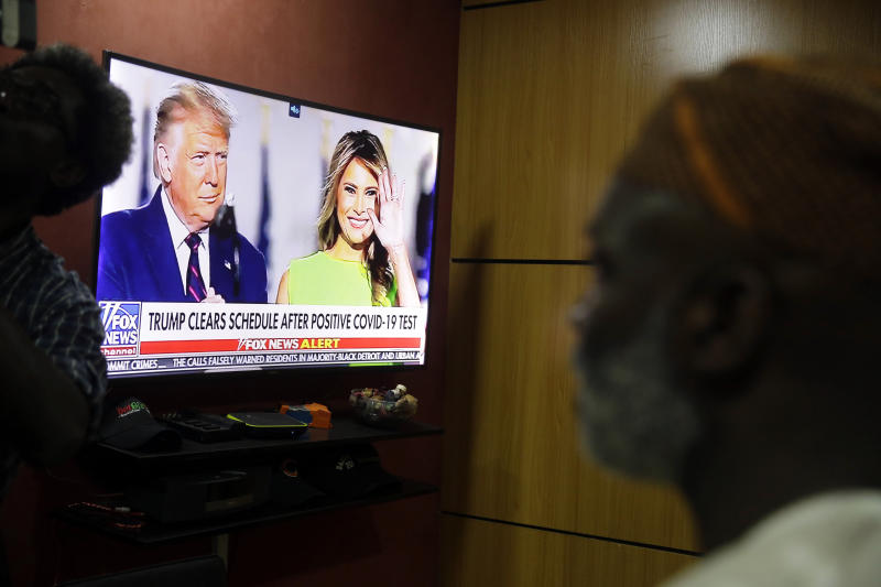 Accountant Abiodun Ayinde watches as the news announces U.S President Donald Trump and First Lady Melania Trump have tested positive for coronavirus, at his office in Lagos Friday, Oct. 2, 2020. Global markets dropped after President Trump said that he and the first lady had tested positive for the coronavirus. (AP Photo/Sunday Alamba)