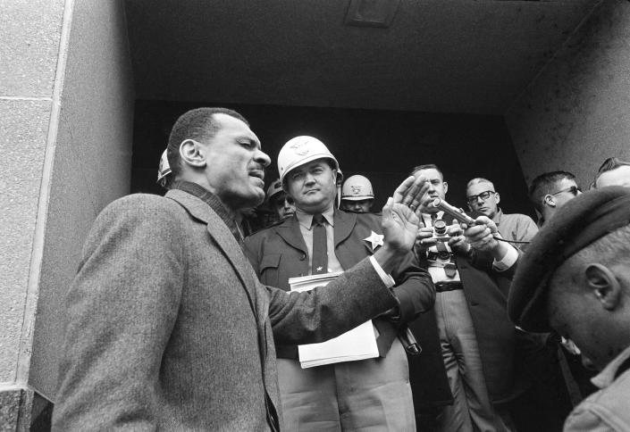 FILE - In this Feb. 5, 1965, file photo, C.T. Vivian, left, leads a prayer on the courthouse steps in Selma, Ala., after Sheriff James Clark, background with helmet, stopped him at the door with a court order. Vivian led hundreds of demonstrators carrying petitions asking for longer voter registration hours. A civil rights veteran, Vivian, who worked alongside the Rev. Martin Luther King Jr., and served as head of the organization co-founded by the civil rights icon, was awarded the Presidential Medal of Freedom and died in July 2020 in Atlanta. Jackson, Mississippi's current mayor declared Wednesday, May 26, 2021, as C.T. Vivian Day in the state's capital city. (AP Photo/Horace Cort, File)