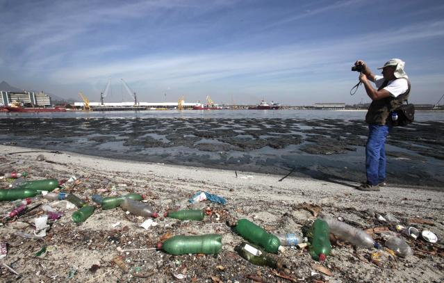 Brazilian biologist Mario Moscatelli takes pictures next to garbage at Pombeba island in the Guanabara Bay in Rio de Janeiro