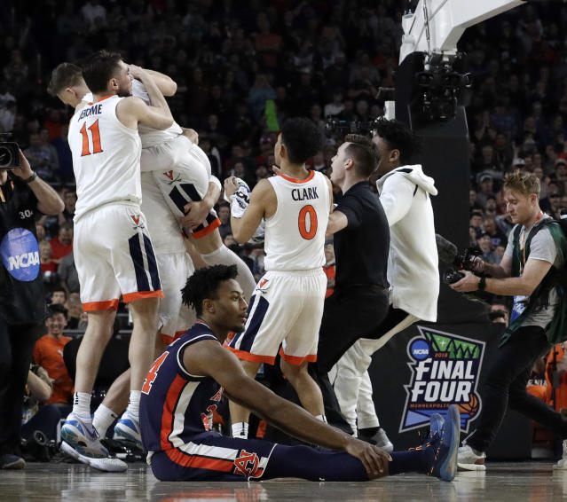 Auburn's Anfernee McLemore (24) reacts on the floor as Virginia celebrate after defeating Auburn 63-62 in the semifinals of the Final Four NCAA college basketball tournament, Saturday, April 6, 2019, in Minneapolis. (AP Photo/David J. Phillip)