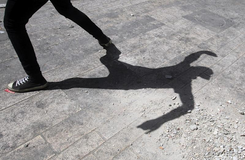 A Palestinian protester hurls a rock at Israeli police (unseen) during clashes in the city of Hebron on April 16, 2014