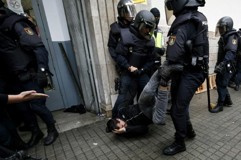 Spanish police officers drag a man as they try to disperse voters arriving to a polling station in Barcelona during the October 1 independence referendum