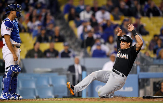 Miami Marlins' Derek Dietrich, right, scores on a double by Starlin Castro as Los Angeles Dodgers catcher Austin Barnes stands at the plate during the eighth inning of a baseball game Tuesday, April 24, 2018, in Los Angeles. (AP Photo/Mark J. Terrill)