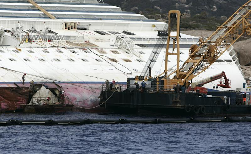 "Workers begin to remove the tons of rocky reef embedded into the Costa Concordia cruise ship's hull, Giglio Island, Italy, Thursday, July 12, 2012. The whole removal process could take as long as a year. In a broadcast interview Tuesday, Concordia's captain Francesco Schettino described the collision as a ""banal accident"" in which ""destiny"" played a role. (AP Photo/Gregorio Borgia)"