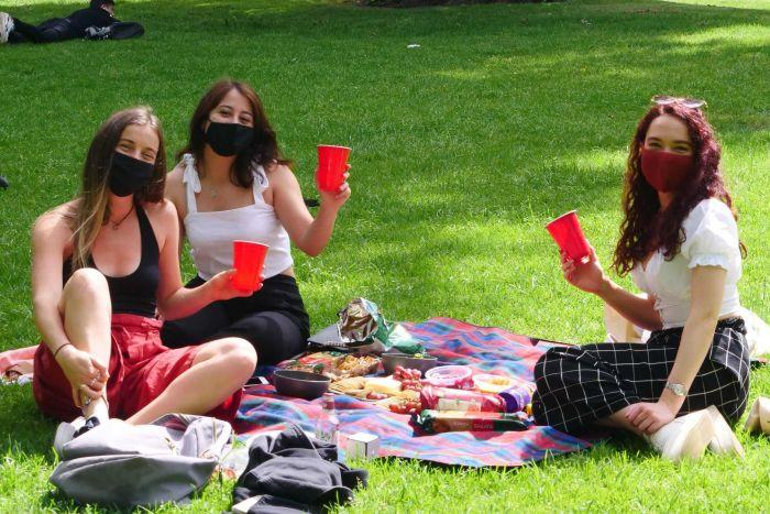 Three young women wearing face masks hold up cups happily in a park.