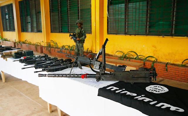 <p>A Philippine Marine guards the display of high-powered firearms, ammunitions, uniforms and black ISIS-style flags which were recovered from Muslim militants Tuesday, May 30, 2017 in Marawi city southern Philippines. Philippine forces pressed their offensive to drive out militants linked to the Islamic State group after days of fighting left corpses in the streets and hundreds of civilians begging for rescue from a besieged southern city of Marawi. (Bullit Marquez/AP) </p>