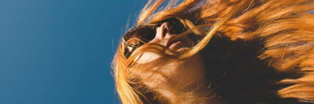 looking up at woman with red hair and sunglasses