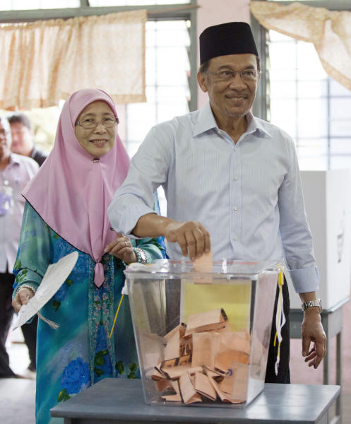 Malaysian opposition leader Anwar Ibrahim votes with his wife Wan Azizah at a polling station at Penanti in Penang state in northern Malaysia, Sunday, May 5, 2013. Malaysian's go to the polls Sundy in what could be the toughest test of the ruling coalition's 56-year grip on power in Southeast Asia's third-largest economy. (AP Photo/Mark Baker)