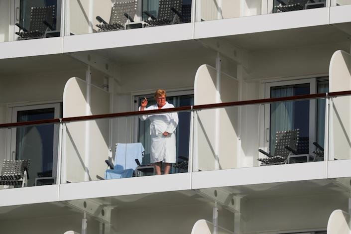 This image shows a person in a robe waving from a balcony of a cruise ship.