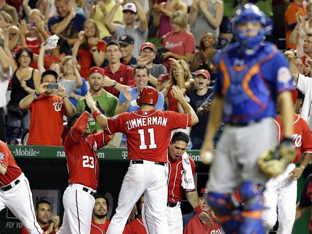 Washington Nationals' Ryan Zimmerman (11) celebrates scoring the winning run during the eighth inning of a baseball game against the New York Mets at Nationals Park, Sunday, Sept. 1, 2013, in Washington. The Nationals won 6-5. (AP Photo/Alex Brandon)