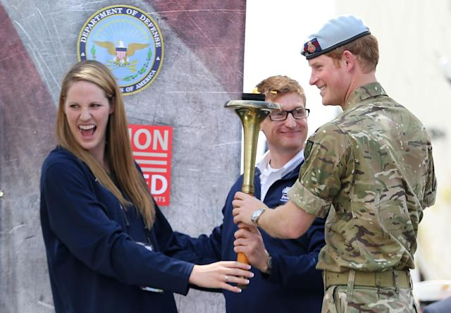 COLORADO SPRINGS, CO - MAY 11: Prince Harry helps to light the flame with US Paralympian Lieutenant Brad Snyder (C) and Olympian Missy Franklin (L) as he attends the Opening Ceremony of the Warrior Games during the third day of his visit to the United States on May 11, 2013 in Colorado Springs, Colorado. HRH will be undertaking engagements on behalf of charities with which the Prince is closely associated on behalf also of HM Government, with a central theme of supporting injured service personnel from the UK and US forces. (Photo by Chris Jackson/Getty Images)