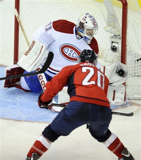Montreal Canadiens goalie Carey Price, top, stops the puck as Washington Capitals left wing Troy Brouwer (20) looks on during the second period of an NHL hockey game on Friday, Feb. 24, 2012, in Washington. (AP Photo/Nick Wass)