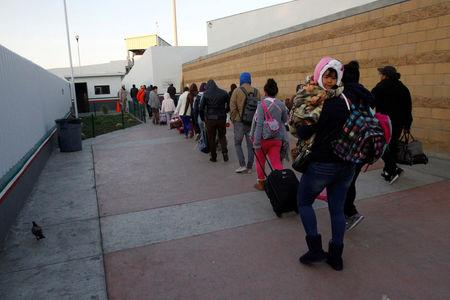 FILE PHOTO: Immigrants from Central America and Mexican citizens, who are fleeing from violence and poverty, queue to cross into the U.S. to apply for asylum at the new border crossing of El Chaparral in Tijuana