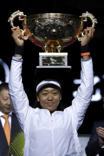 Naomi Osaka of Japan lifts-up her winner's trophy after defeating Ashleigh Barty of Australia in the women's final at the China Open tennis tournament in Beijing, Sunday, Oct. 6, 2019. (AP Photo/Mark Schiefelbein)