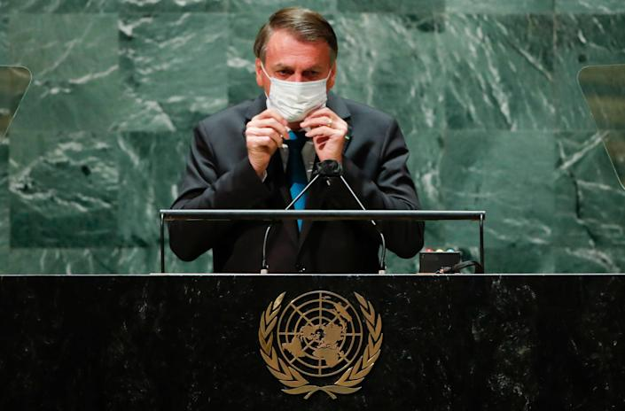File: Brazil's president Jair Bolsonaro puts on a protective face mask after speaking at the 76th Session of the UN General Assembly in New York on 21 September 2021 (ASSOCIATED PRESS)