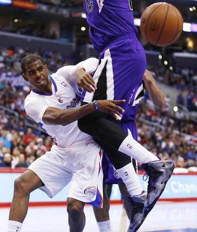 Los Angeles Clippers guard Chris Paul passes the ball around Sacramento Kings center DeMarcus Cousins during the first half of an NBA basketball game in Los Angeles, Sunday, April 12, 2014. (AP Photo/Danny Moloshok)