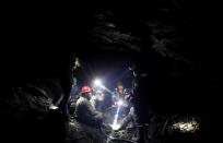 FILE PHOTO: Miners talk to each other as they sit inside a gold mine in La Rinconada
