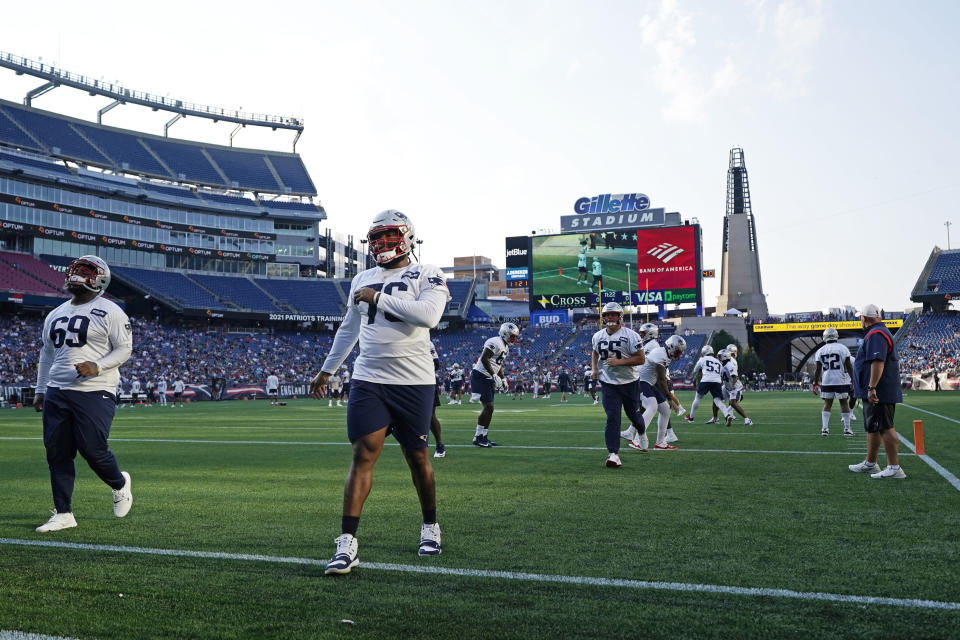 New England Patriots players warm up at Gillette Stadium during an NFL football practice, Friday, Aug. 6, 2021, in Foxborough, Mass. (AP Photo/Elise Amendola)