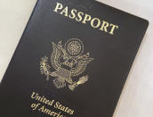 FILE - This May 25, 2021, file photo shows a U.S. Passport cover in Washington. Americans hoping to travel abroad this summer may have to delay their plans if they need new or renewed passports. Would-be travelers are overwhelming federal offices as the lifting of COVID-19 travel restrictions unleashes a pent-up demand for passports. Wait times for new passports and renewals are now up to 18 weeks and those seeking expedited appointments can take up to 12 weeks. (AP Photo/Eileen Putman, File)