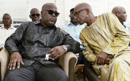 Felix Tshisekedi talks to an unidentified visitor as he mourns the death of his father and veteran Congolese opposition leader Etienne Tshisekedi, in the courtyard of his residence in the Limete Municipality of the DRC's capital Kinshasa