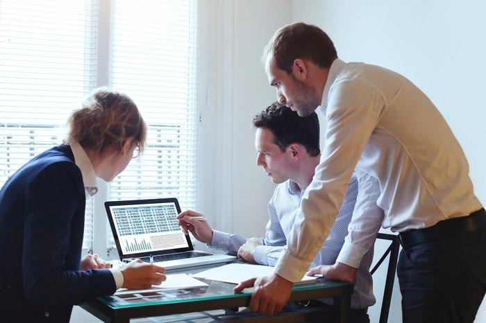 A group of three office workers gathered around a computer looking at charts.