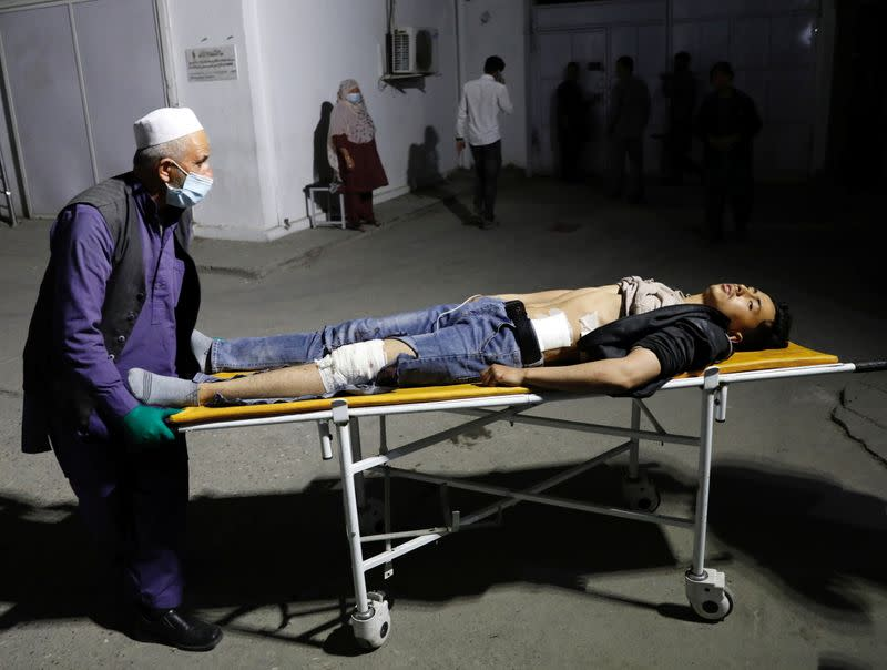 An Afghan man wheels an injured man in a hospital after a suicide bombing in Kabul