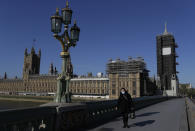 A woman walks near Britain's Houses of Parliament as the country is in lockdown to help curb the spread of coronavirus, in London, Tuesday, April 21, 2020. Britain's Parliament is going back to work, and the political authorities have a message for lawmakers: Stay away. U.K. legislators and most parliamentary staff were sent home in late March as part of a nationwide lockdown to slow the spread of the new coronavirus. With more than 16,500 people dead and criticism growing of the government's response to the pandemic, legislators are returning Tuesday — at least virtually — to grapple with the crisis. (AP Photo/Kirsty Wigglesworth)