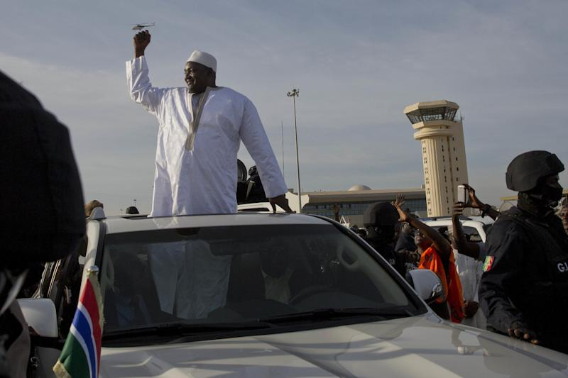Gambian President Adama Barrow greets the crowds after arriving at Banjul airport in Gambia, Thursday Jan. 26, 2017, after flying in from Dakar, Senegal Gambia's new president has finally arrived in the country, a week after taking the oath of office abroad amid a whirlwind political crisis. Here's a look at the tumble of events that led to Adama Barrow's return — and the exile of the country's longtime leader. (AP Photo/Jerome Delay)
